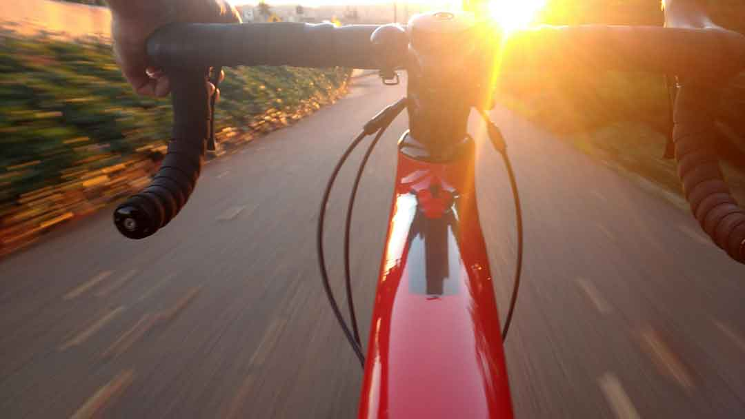 A person is enjoying a bike tour toward the sunrise, one of the amazing things to do in Almancil